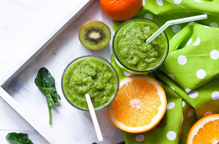 fresh green smoothie on tray with kiwi and orange slice
